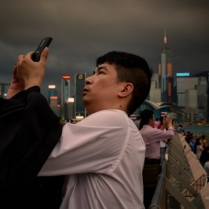 A man takes a selfies near Victoria Harbour in Hong Kong