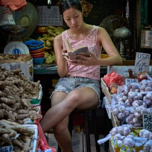 A young woman in market reading at her stall on Reclamation Street in Hong Kong