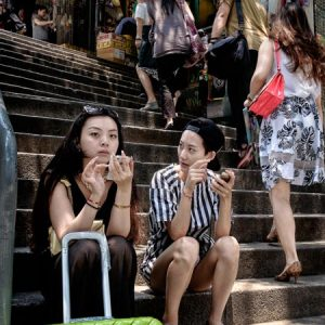 Two young Chinese tourists take a seat on the steps that form part of Pottinger Street in Hong Kong