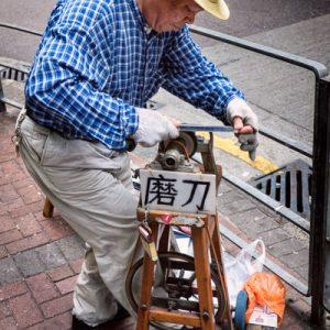 A knife grinder at work in Tai Kok Tsui, Hong Kong