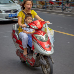 A woman and child on their moped commuting in Shanghai #058
