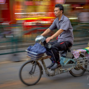 A commuter travelling on his moped in the early evening in Shanghai #035