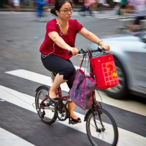 A lady cyclist makes her way through traffic while commuting in Shanghai #063