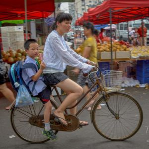 A woman and child commuting on a moped through a fresh produce market in Shanghai #267