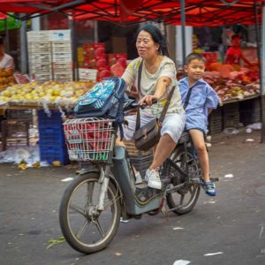 A woman and child commuting on a moped through a fresh produce market in Shanghai #299