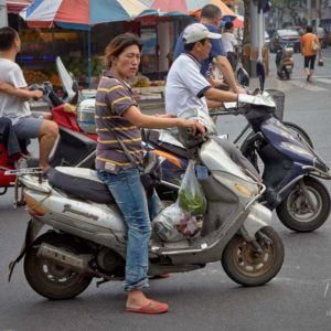 Commuters on their mopeds wait for the traffic lights to change at an intersection in Shanghai #341