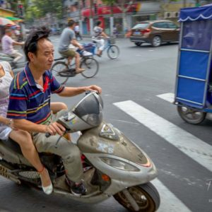 A couple commuting on their moped in Shanghai #348